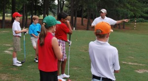 At the Marietta Golf and Country Club, junior golfers start early and are taught the basics of golf. Every Saturday at 9 a.m. to 10:30 a.m. the club has a junior camp. Here, coach Graham Thatcher explains what to be aware of when hitting a driver. Photo by Mette Pedersen
