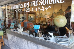 Display of various antiques for sale through the front window glass of Antiques on the Square. Photo by James White
